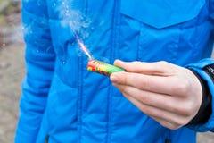 Mano que sostiene el fuego artificial ardiente delante de la chaqueta azul Imagenes de archivo