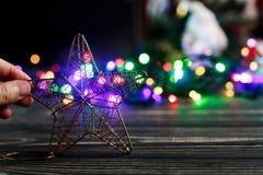 Mano que sostiene el juguete de oro de la estrella de la Navidad en el fondo de colorido Fotografía de archivo libre de regalías