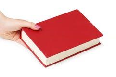 Mano que sostiene el libro rojo aislado Imágenes de archivo libres de regalías