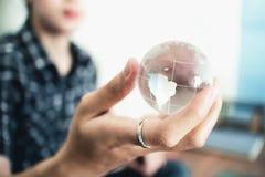 Mano que sostiene el mundo cristalino S?mbolo del negocio foto de archivo