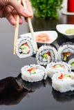 Mano que sostiene el palillo con el conjunto del sushi del maki Fotos de archivo libres de regalías