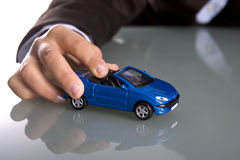 Mano que sostiene el pequeño coche azul Imagen de archivo