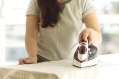 Mano que sostiene el primer del hierro, muchacha que frota ligeramente la camisa blanca de la ropa en un fondo ligero imagen de archivo