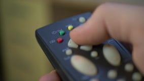 Mano que sostiene el regulador remoto negro y los botones de la TV metrajes