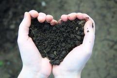 Mano que sostiene el suelo negro bajo la forma de corazón Fotos de archivo libres de regalías