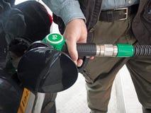 Mano que sostiene el surtidor de gasolina Foto de archivo libre de regalías