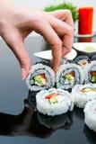 Mano que sostiene el sushi en fondo negro Imagenes de archivo