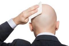 Mano que sostiene el tejido que limpia o que seca la cabeza calva del sudor Imagen de archivo libre de regalías