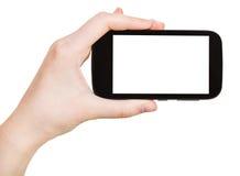 Mano que sostiene el teléfono elegante aislado en blanco Imagen de archivo