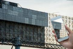 Mano que sostiene el teléfono elegante en las banderas Imagen de archivo