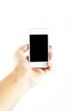 Mano que sostiene el teléfono elegante móvil foto de archivo libre de regalías
