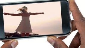 Mano que sostiene el teléfono móvil con el baile de la mujer almacen de metraje de vídeo