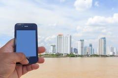 Mano que sostiene el teléfono móvil con el fondo de la ciudad imagen de archivo libre de regalías