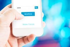 Mano que sostiene el teléfono móvil con la página de la búsqueda en la pantalla con el móvil Foto de archivo libre de regalías