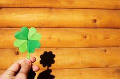 Mano que sostiene el trébol verde de la papiroflexia de papel Foto de archivo