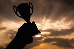 Mano que sostiene el trofeo del ganador imagenes de archivo