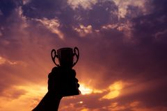Mano que sostiene el trofeo del ganador imagen de archivo