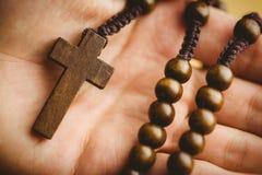 Mano que sostiene gotas de madera del rosario Fotos de archivo