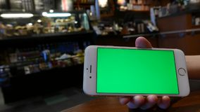 Mano que sostiene iphone verde de la pantalla