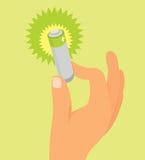 Mano que sostiene la batería verde Imagen de archivo