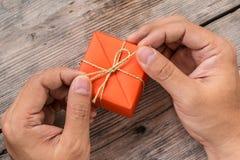 Mano que sostiene la caja de regalo anaranjada y la cinta amarilla Fotos de archivo libres de regalías