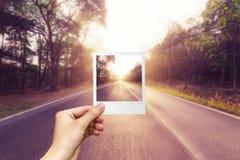 Mano que sostiene la carretera de asfalto vacía del marco de la foto Imagen de archivo libre de regalías