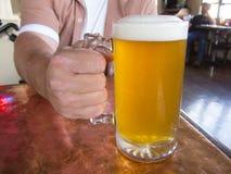 Mano que sostiene la cerveza Imagen de archivo