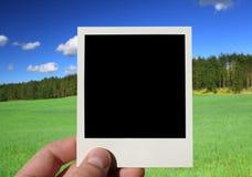 Mano que sostiene la foto en blanco Imagenes de archivo
