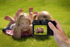 Mano que sostiene la fotografía de la cámara de niñas lindas Foto de archivo