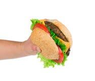 Mano que sostiene la hamburguesa grande en el fondo blanco Foto de archivo libre de regalías