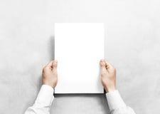 Mano que sostiene la maqueta blanca de la hoja del papel en blanco, imagen de archivo