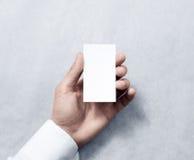 Mano que sostiene la maqueta blanca vertical en blanco del diseño de la tarjeta de visita Fotos de archivo