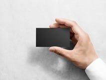 Mano que sostiene la maqueta negra llana en blanco del diseño de la tarjeta de visita Imagenes de archivo