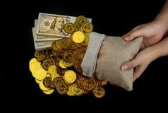 Mano que sostiene la moneda de oro en los paquetes del saco y de la pila del tesoro de 100 dólares americanos de billetes de banc fotografía de archivo libre de regalías