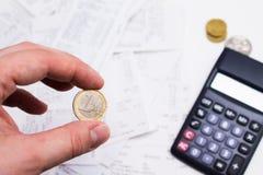 Mano que sostiene la moneda y la calculadora en fondo Imagenes de archivo
