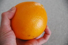 Mano que sostiene la naranja sin pelar Fotografía de archivo