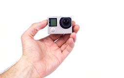 Mano que sostiene la pequeña cámara de la acción Foto de archivo