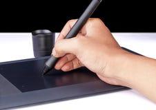 Mano que sostiene la tableta del dibujo para el diseñador gráfico Imágenes de archivo libres de regalías