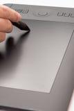 Mano que sostiene la tableta del dibujo para el diseñador gráfico imagenes de archivo