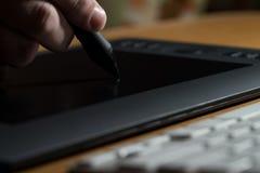 Mano que sostiene la tableta del dibujo para el diseñador gráfico foto de archivo
