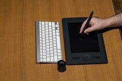 Mano que sostiene la tableta del dibujo para el diseñador gráfico imagen de archivo