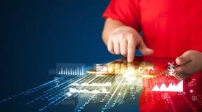 Mano que sostiene la tableta del panel táctil con los gráficos del mercado empresarial Imagen de archivo