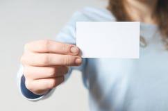 Mano que sostiene la tarjeta de visita en blanco Foto de archivo libre de regalías