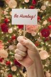 Mano que sostiene la tarjeta del embaucamiento de los vagos delante del árbol de navidad adornado Imágenes de archivo libres de regalías