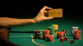 Mano que sostiene la tarjeta del oro, microprocesadores de juego en la tabla, casino ilegal para los VIP-clientes almacen de metraje de vídeo