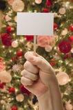 Mano que sostiene la tarjeta en blanco delante del árbol de navidad adornado Imagen de archivo libre de regalías