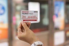 Mano que sostiene la tarjeta tur?stica del paso de Singapur en el ferrocarril del MRT; Singapur, el 9 de mayo de 2019 foto de archivo