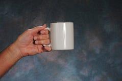 Mano que sostiene la taza Imagen de archivo libre de regalías