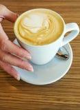 Mano que sostiene la taza del café con leche Fotografía de archivo