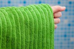 Mano que sostiene la toalla verde Imagenes de archivo